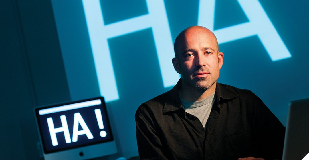 """Image of Dave Ciccoricco sitting in front of visual rendering of the word """"HA!"""""""