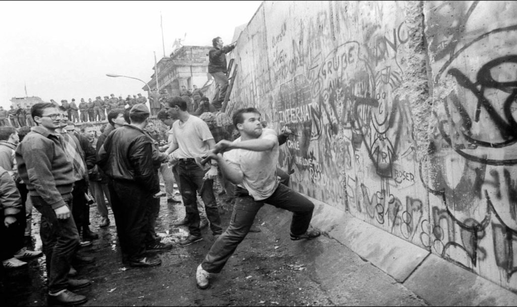 Black and white photo of man attempting to knock down Berlin wall in hammer.